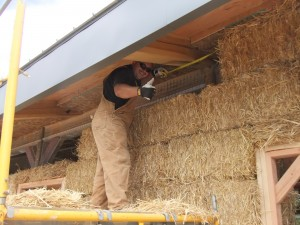 man installing straw bale on top course
