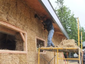man smoothing straw bale house wall