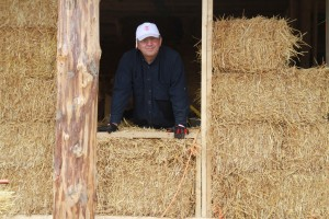 man standing by straw bale window