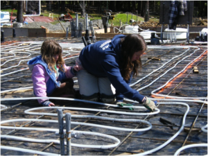 woman and child installing radiant floor heat tubing