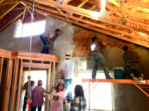 People applying plaster to straw bale walls