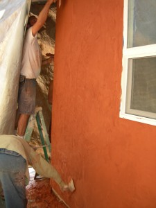 people plastering straw bale house