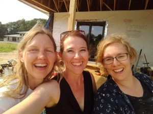 Happy women in front of straw bale house