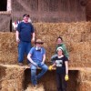 three people on straw bales