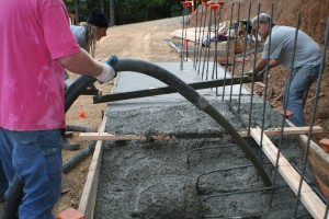 men pouring concrete footers