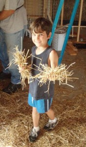 child holding handfuls of straw