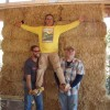 three men in front of a straw bale wall