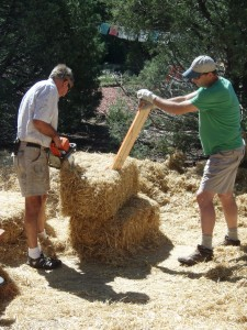two men cutting a straw bale