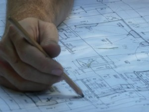 hand with pencil on construction drawings