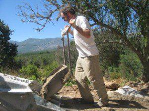 Andrew Morrison adding sand to plaster machine via sand sled