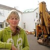 woman and backhoe in front of house