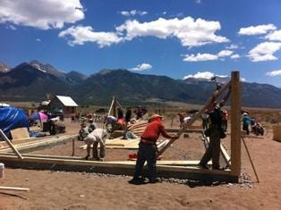 Men setting corner studs on a straw bale house