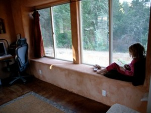 girl sitting on straw bale window seat