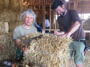 Happy people cutting a straw bale