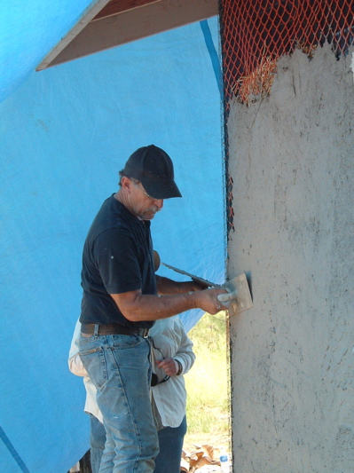 man plastering straw bale house