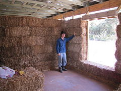 Man in front of a straw bale wall at the eco farm stay