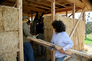 woman building straw bale house