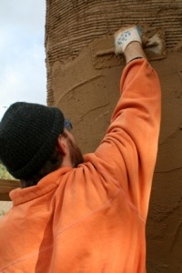man plastering straw bale wall