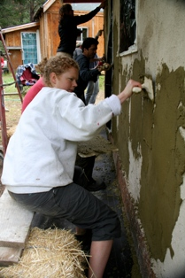 woman applying final plaster on straw bale wall