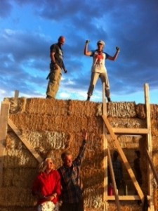 people standing atop straw bale wall