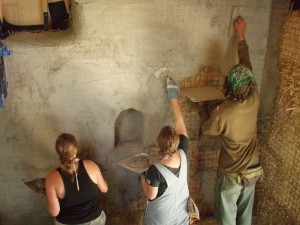 people plastering straw bale wall