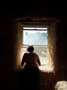woman shaping straw bale wall