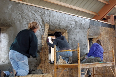 people plastering a straw bale house