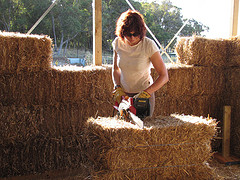 woman cutting straw bales at workshop