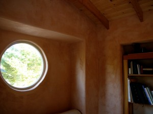 round window straw bale cabin