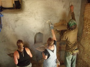 Three people plastering a straw bale house